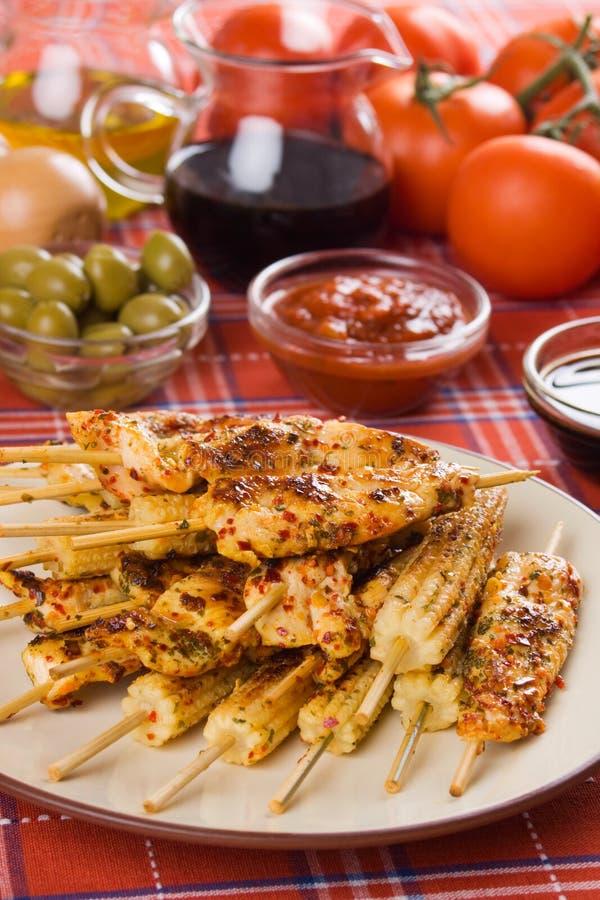 Carne del pollo y maíz de bebé asados a la parilla fotografía de archivo libre de regalías