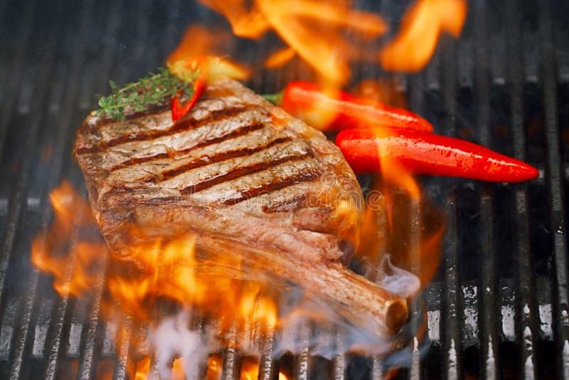 Carne dell'alimento - bistecca di manzo sulla griglia del barbecue del bbq con la fiamma fotografia stock