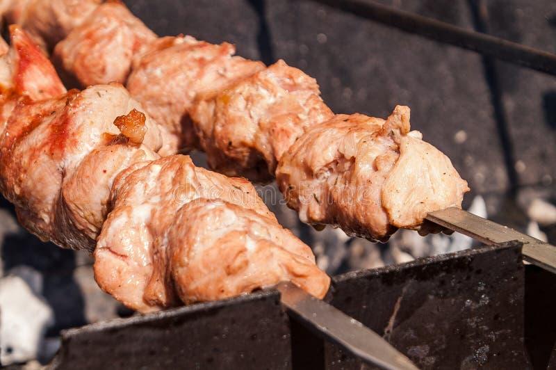 carne dell'arrosto sugli spiedi su fuoco aperto immagini stock