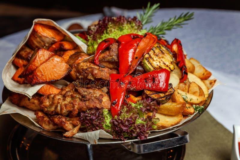Carne dell'assortimento di grigliate, verdure fritte e decorazione di color salmone arrostita dei filetti di pesce in piatto cald fotografia stock