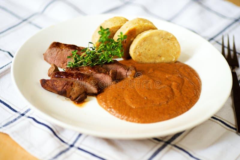 Carne di cervo, salsa del prugna-pan di zenzero e gnocco sul piatto fotografia stock