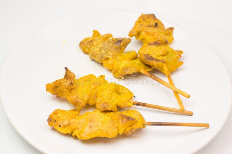 Carne di maiale arrostita satay con la salsa e l'aceto dell'arachide sul piatto bianco e sull'isolato bianco del fondo fotografia stock libera da diritti