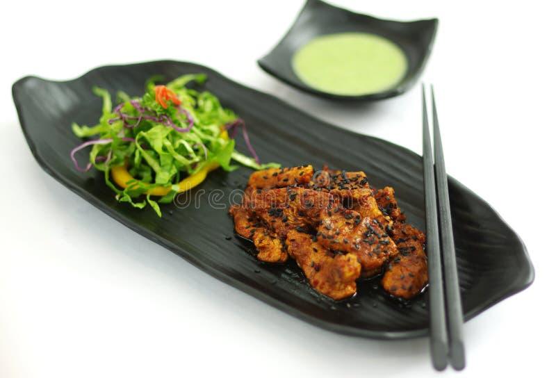 Carne di maiale brasata con la salsa di peperoncino rosso, il seasame e l'insalata su platte nera fotografia stock libera da diritti