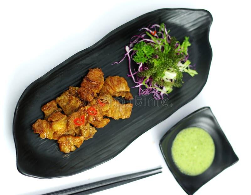 Carne di maiale brasata con la salsa e l'insalata di peperoncino rosso sul vassoio nero immagine stock libera da diritti