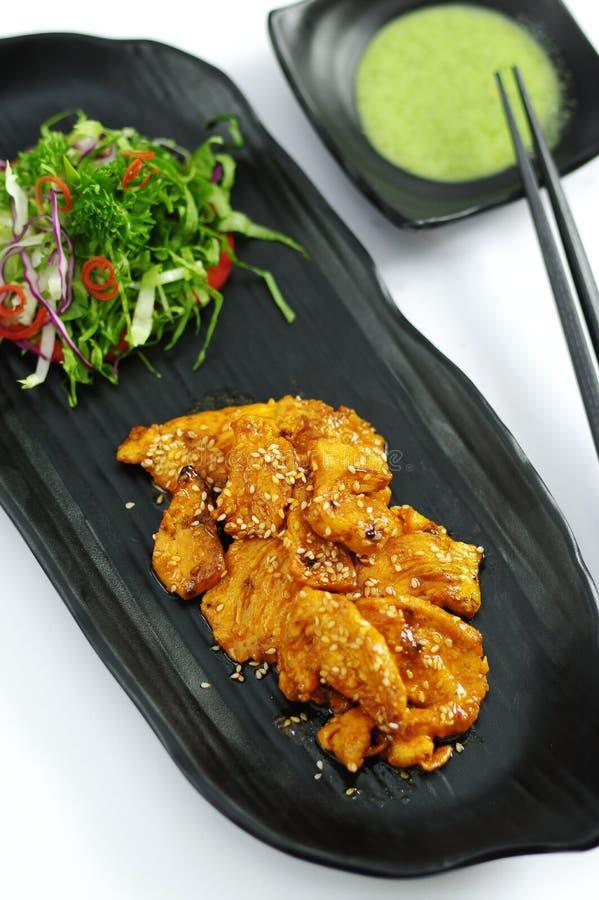 Carne di maiale brasata con la salsa e l'insalata di peperoncino rosso sul vassoio nero fotografia stock libera da diritti
