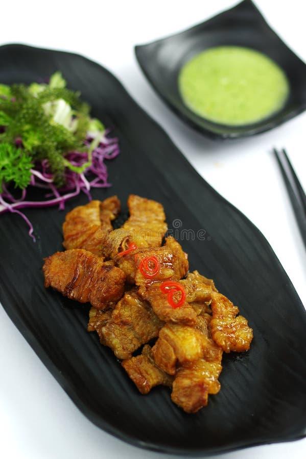 Carne di maiale brasata con la salsa e l'insalata di peperoncino rosso sul vassoio nero immagini stock