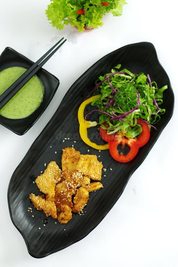 Carne di maiale brasata con la salsa e l'insalata di peperoncino rosso sul vassoio nero fotografie stock libere da diritti