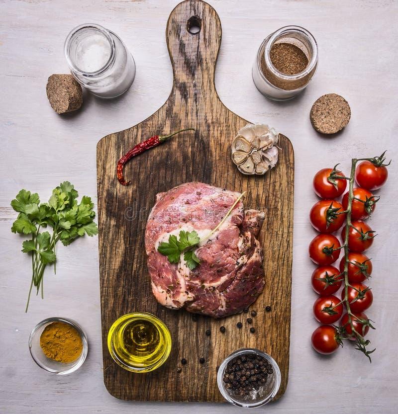 Carne di maiale cruda in marinata, su un tagliere con i pomodori su un ramo, olio, pepe nero, erbe sulla vista superiore del fond immagini stock libere da diritti