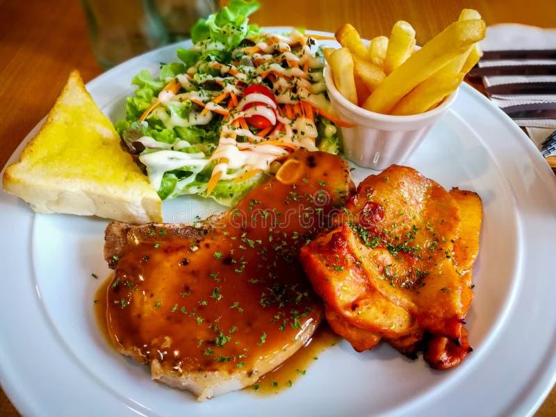 Carne di maiale e bistecca del pollo con insalata, le patate fritte ed il pane tostato fotografia stock