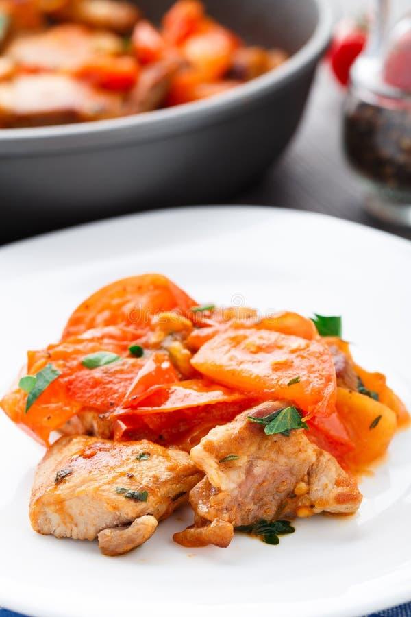 Carne di maiale fritta con i pomodori pan-arrostiti immagini stock