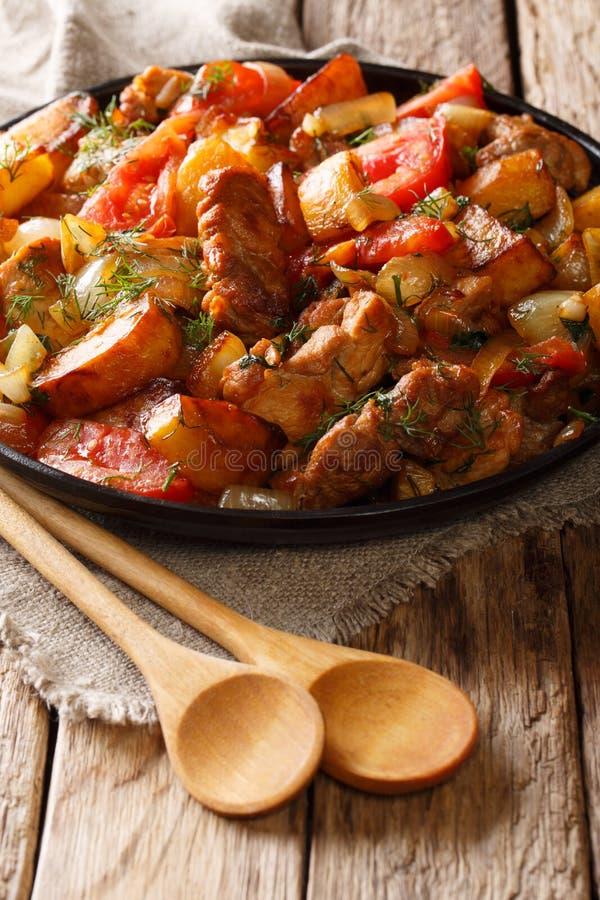 Carne di maiale fritta con le patate, i pomodori ed il primo piano delle spezie su un fryi fotografie stock