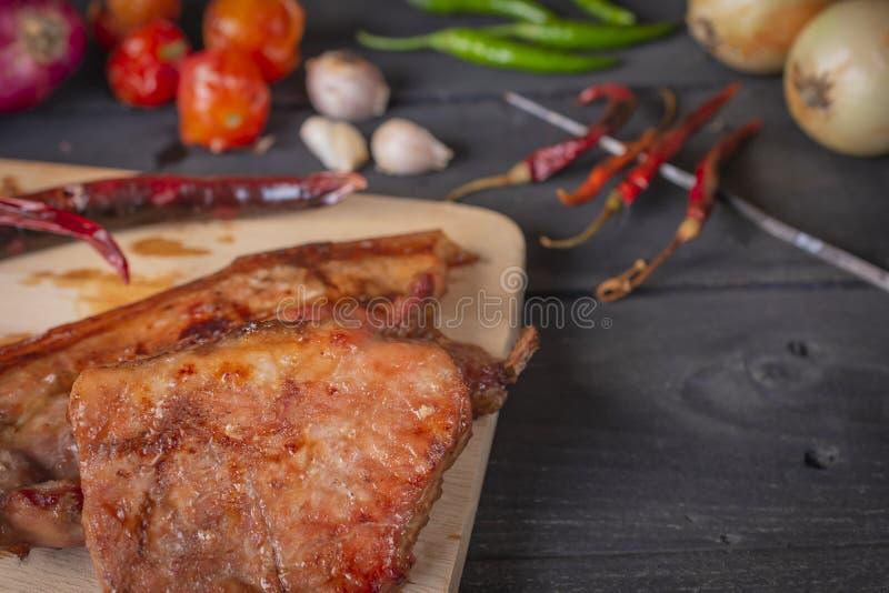 Carne di maiale grigliata sul tagliere, disposto su una tavola di legno con le spezie disposte intorno immagine stock