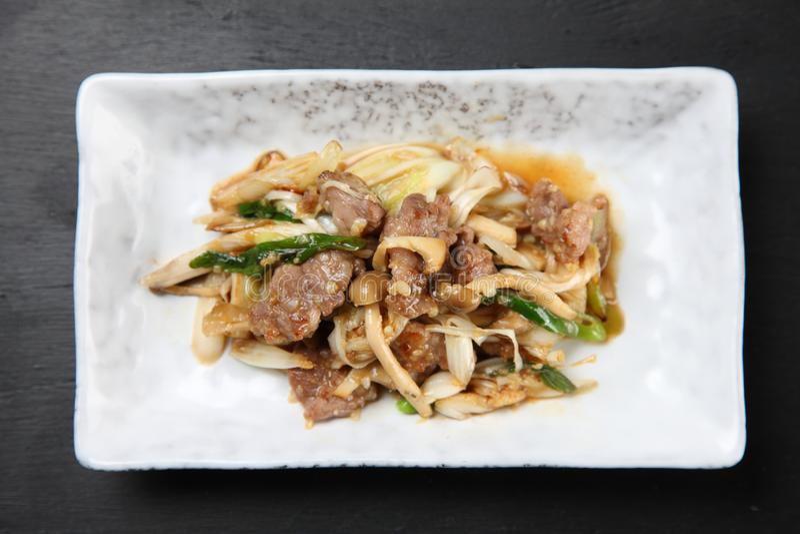 Carne di maiale in padella con il fungo su un tavolo da pranzo fotografia stock