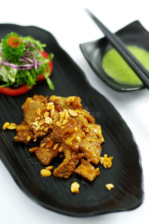 Carne di maiale sauteed con le arachidi e l'insalata sul vassoio nero fotografie stock libere da diritti