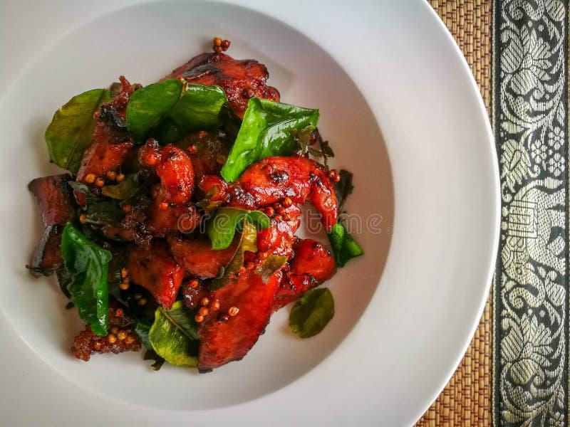Carne di maiale seccata al sole fritta nel grasso bollente sul piatto con la foglia della calce del kafflir fotografie stock libere da diritti
