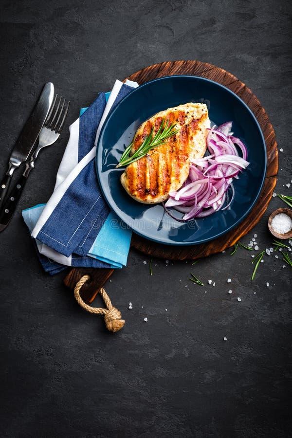 Carne di pollo arrostita succosa, raccordo con la cipolla marinata fresca sul piatto Fondo nero, vista superiore, primo piano fotografia stock