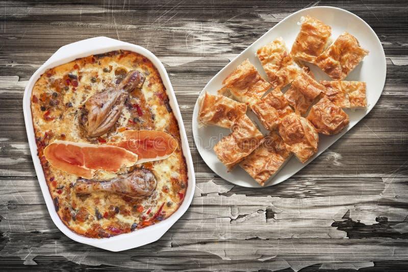 Carne di pollo con le fette di verdure della torta del formaggio di Gibanica e dello stufato in vassoi sulla vecchia Tabella di l fotografia stock libera da diritti