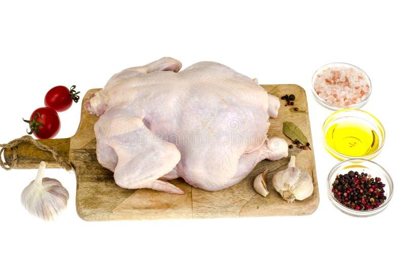 Carne di pollo cruda con le verdure e le spezie sul tagliere, per la cottura, fondo bianco fotografia stock libera da diritti