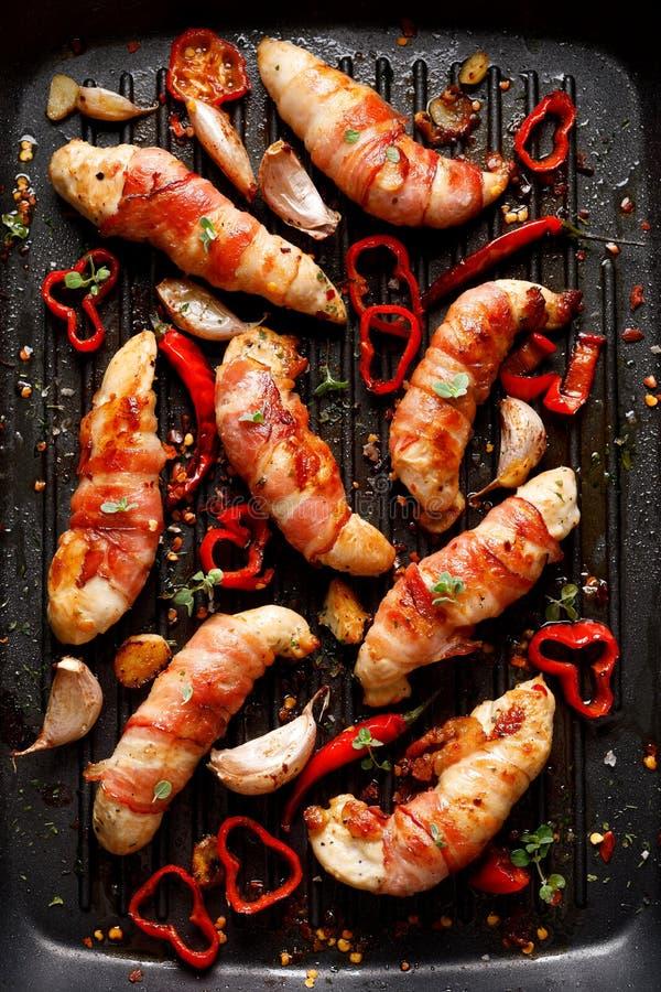 Carne di pollo della spezia, filetto arrostito del pollo avvolto con bacon con i peperoncini dell'aggiunta, aglio ed erbe sul pia immagine stock