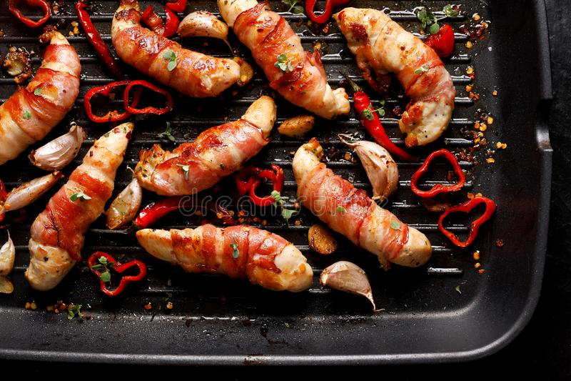 Carne di pollo della spezia, filetto arrostito del pollo avvolto con bacon con i peperoncini dell'aggiunta, aglio ed erbe sul pia immagini stock