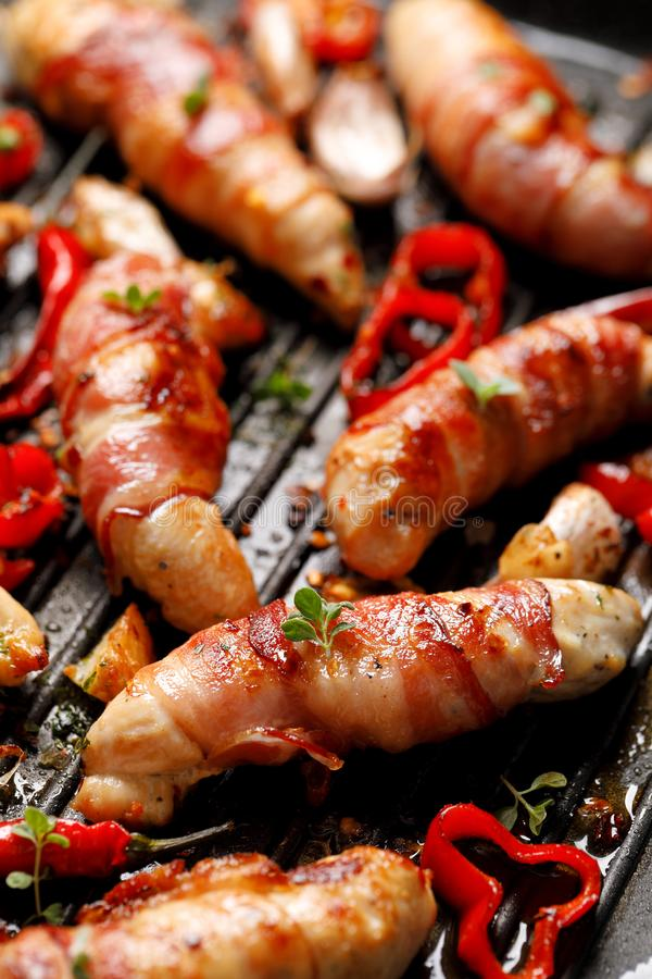 Carne di pollo della spezia, filetto arrostito del pollo avvolto con bacon con i peperoncini dell'aggiunta, aglio ed erbe sul pia fotografia stock