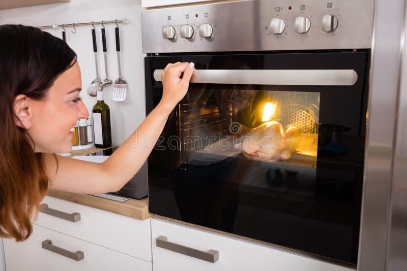 Carne di pollo di torrefazione della donna in forno fotografia stock libera da diritti