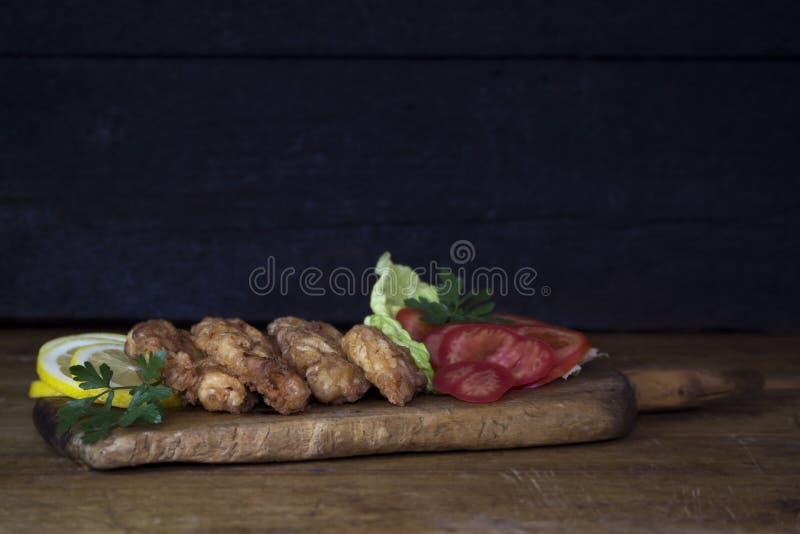 Carne di pollo impanata con insalata ed il limone che riposano su un Wo rustico fotografia stock