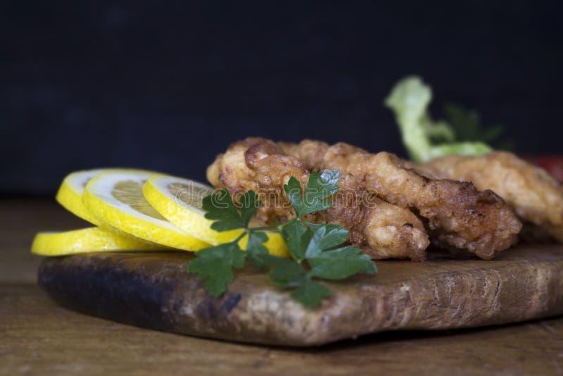 Carne di pollo impanata con insalata ed il limone che riposano su un Wo rustico fotografia stock libera da diritti
