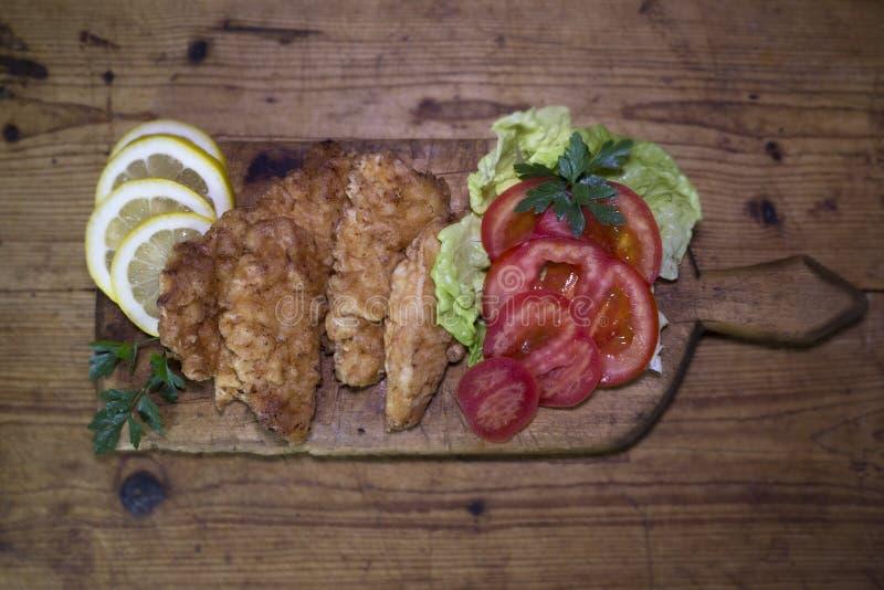 Carne di pollo impanata con insalata ed il limone che riposano su un Wo rustico immagine stock libera da diritti