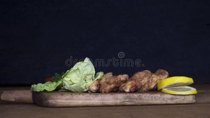 Carne di pollo impanata con insalata ed il limone che riposano su un Wo rustico immagini stock