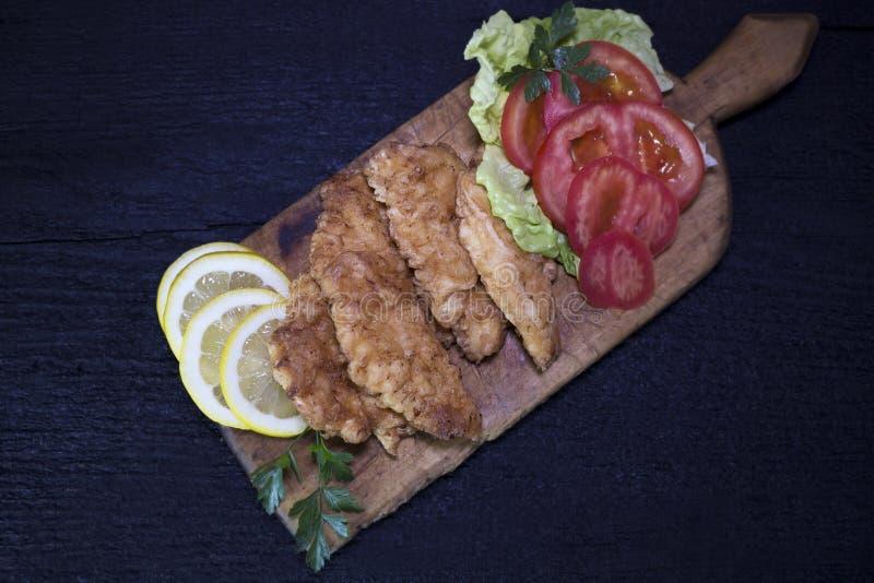 Carne di pollo impanata con insalata ed il limone che riposano su un Wo rustico fotografie stock