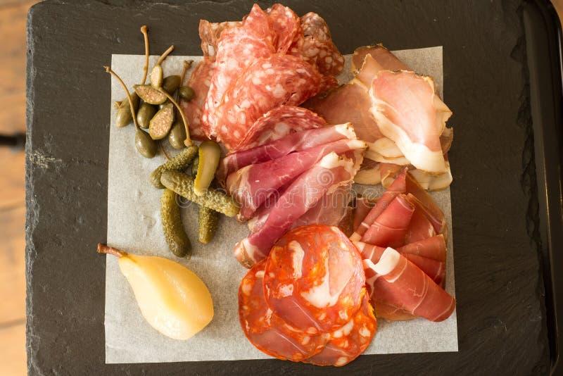 Carne di pranzo e sottaceti e frutti affettati sull'ardesia immagini stock