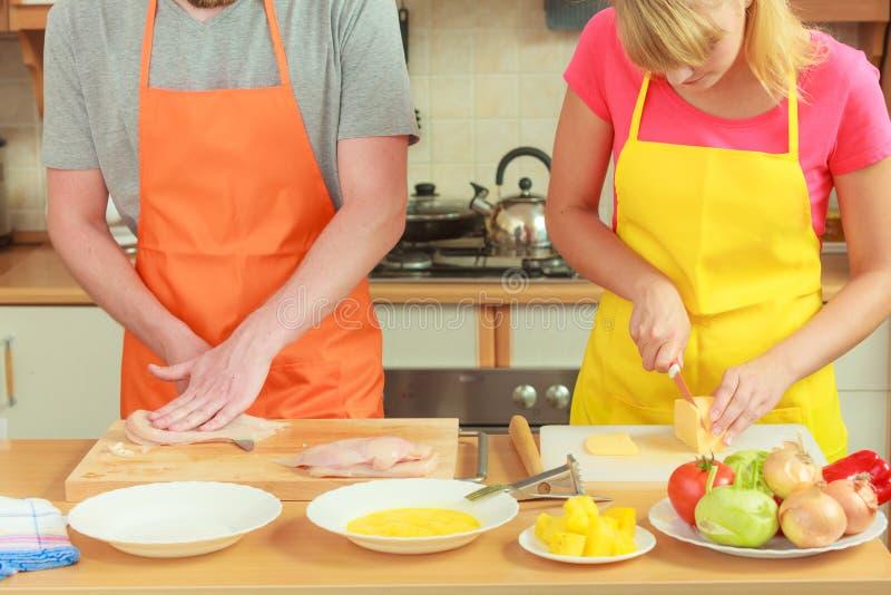 Carne di taglio dell'uomo a bordo Coppie in cucina fotografia stock libera da diritti