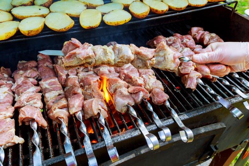 Carne do assado do churrasco no carvão de madeira O homem cozinha o no espeto quente apetitoso em espetos do metal imagem de stock