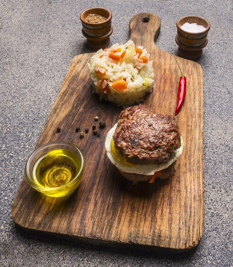 Carne do hamburguer somente e ovos e manteiga apetitosos, com arroz e vegetais, especiarias na placa de corte do vintage imagens de stock royalty free