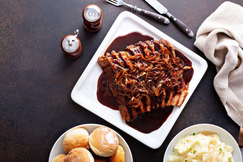 Carne do peito cortada com cebolas caramelizadas imagem de stock royalty free