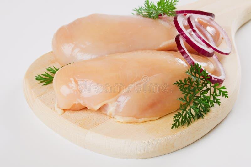 Carne do peito de galinha na placa de madeira imagens de stock