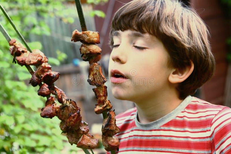 Carne do shashlik do cheiro do menino do Preteen no piquenique do verão fotografia de stock royalty free