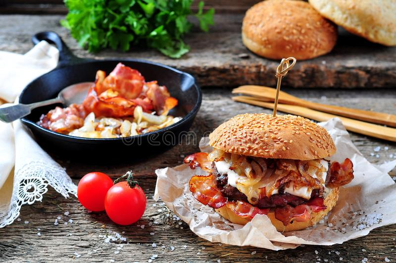 Carne dobro caseiro suculenta do hamburguer com cebolas fritadas em um fundo de madeira fotografia de stock