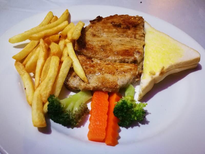 a carne dos peixes da caranga e o bife de costeleta da carne de porco grelhado com a batata do pão da manteiga fritaram e vegetal fotografia de stock royalty free