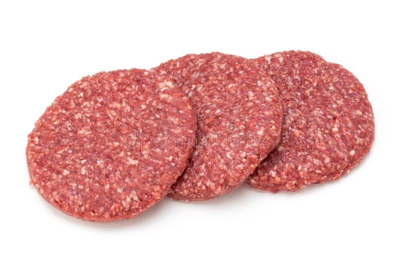 Carne fresca cruda dell'hamburger isolata su bianco immagine stock
