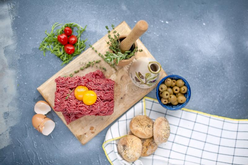 Carne fresca da carne no recheio de carne, em uma placa de madeira Os ovos e os tomates crus são pequenos Ervas para o cozimento  imagens de stock