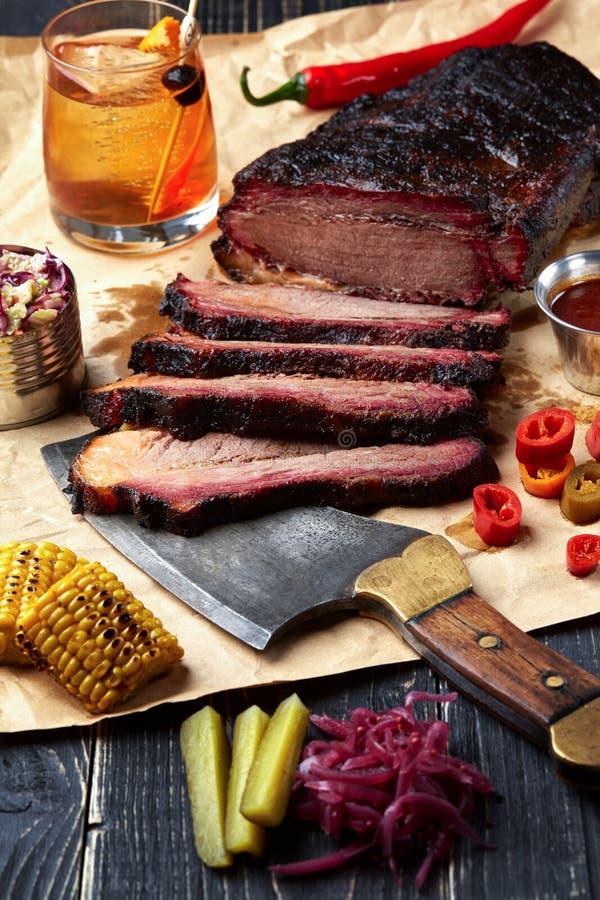 Carne fresca do BBQ da carne do peito cortada servindo contra um fundo do papel de embalagem com molho, pimentos e milho fotos de stock