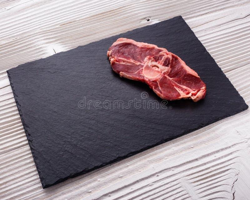 Carne fresca do cordeiro em uma placa de pedra textured imagem de stock