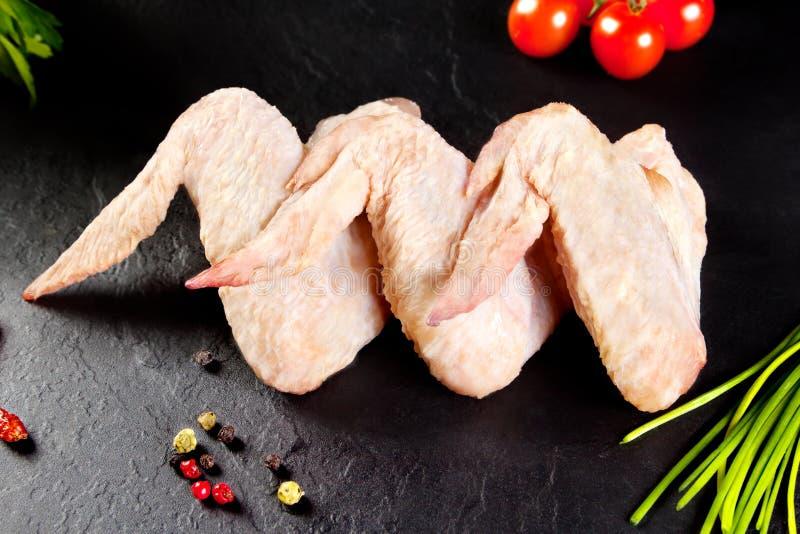 Carne fresca e crua As asas de galinha brancas aprontam-se para cozinhar Quadro-negro preto do fundo fotografia de stock