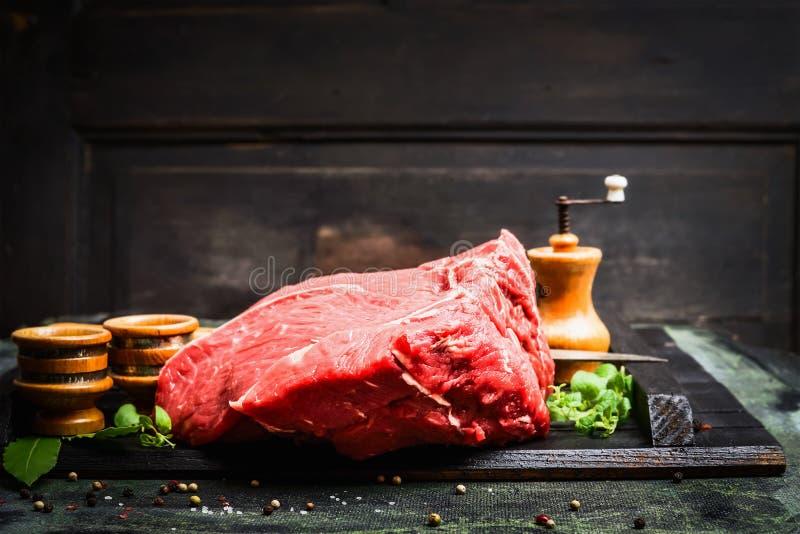Carne fresca para o cozimento saboroso na mesa de cozinha rústica sobre o fundo de madeira escuro imagens de stock royalty free