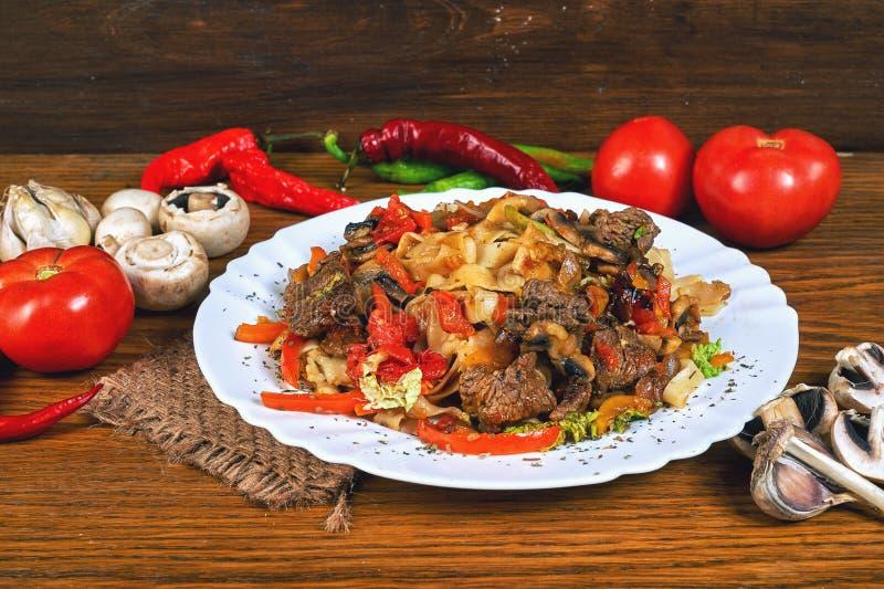 Carne fritada com vegetais em um frigideira do ferro fundido fotografia de stock