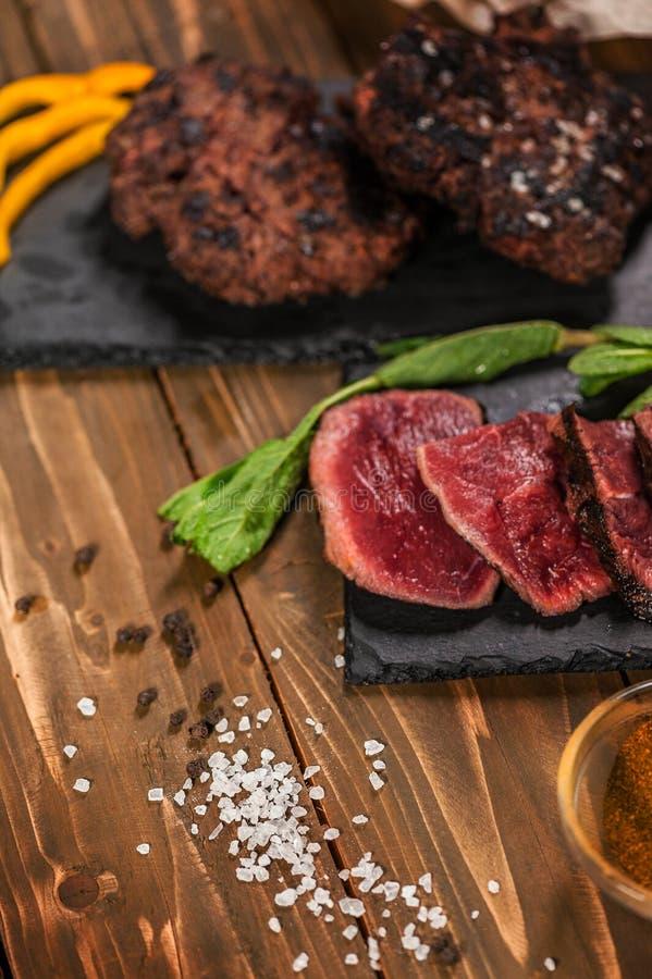 Carne fritada cortada, hamburgueres e estacas Em uma tabela de madeira imagem de stock royalty free