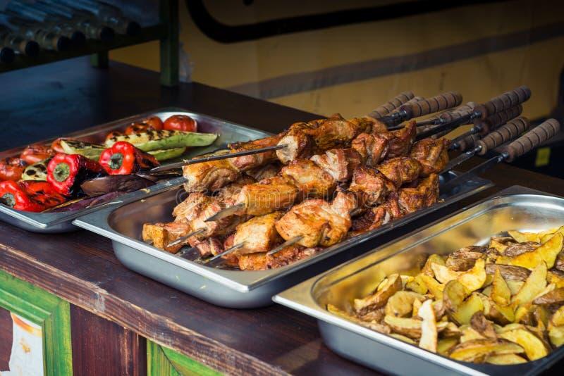 Carne fritada em espetos, e vegetais grelhados em bandejas fotos de stock royalty free