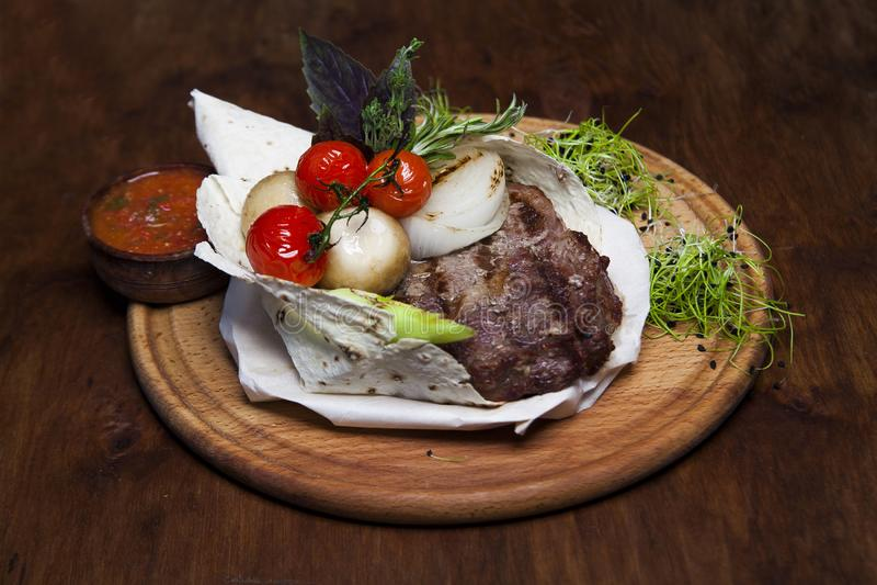 Carne fritada no pão do pão árabe com vegetais, em um varrão de madeira marrom foto de stock